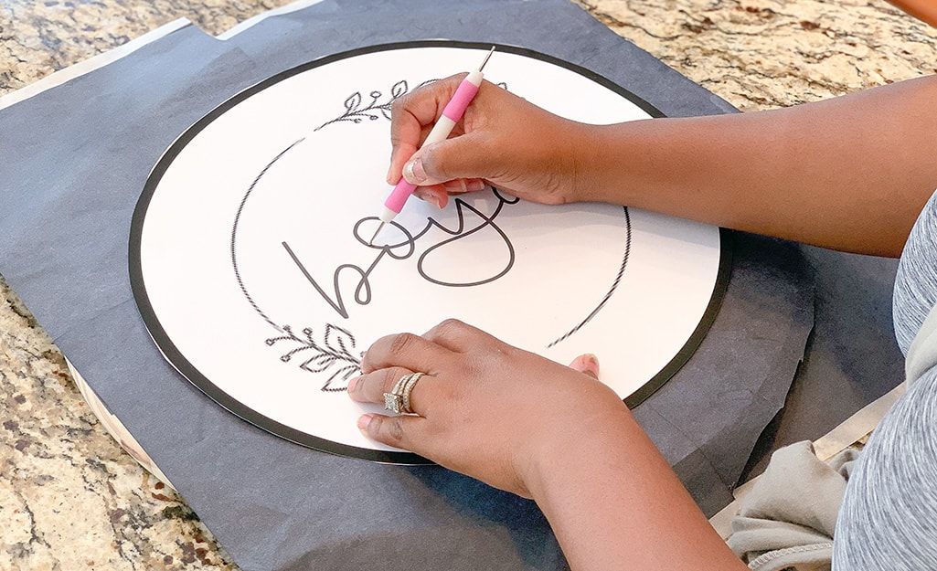 A stylus is used to trace the image onto carbon paper.
