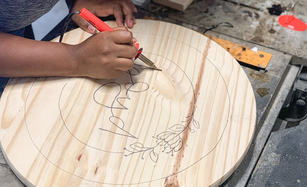 A soldering iron is used to burn the design into the wood round.
