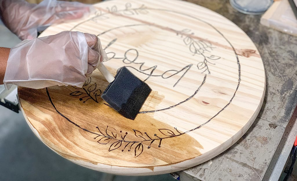 A person uses a sponge brush to stain wood.