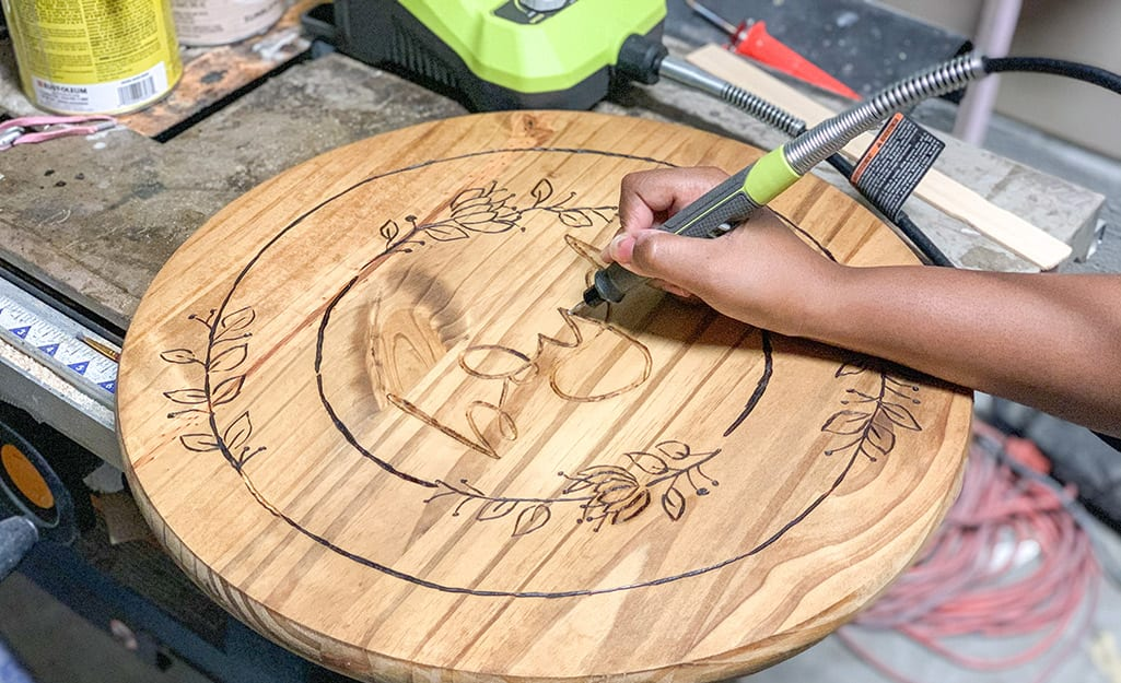 A person uses their rotary tool to carve image into wood.