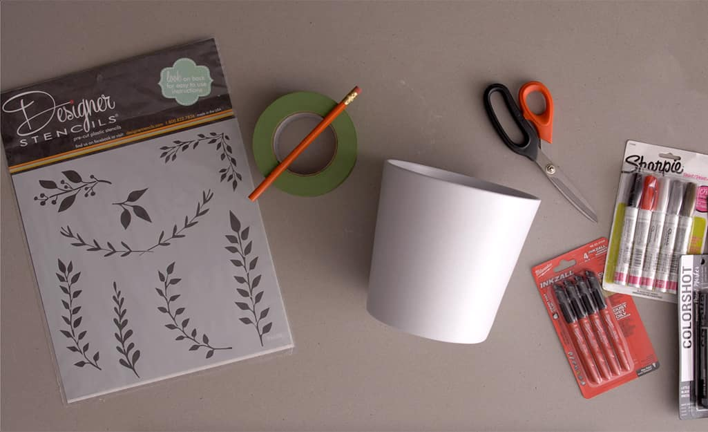Stencils, markers, a plant pot and other supplies gathered on a table.