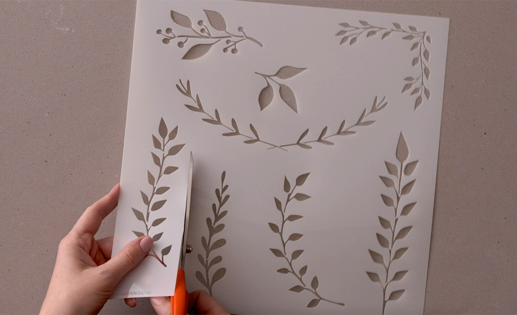 Botanical stencils being cut out with scissors.