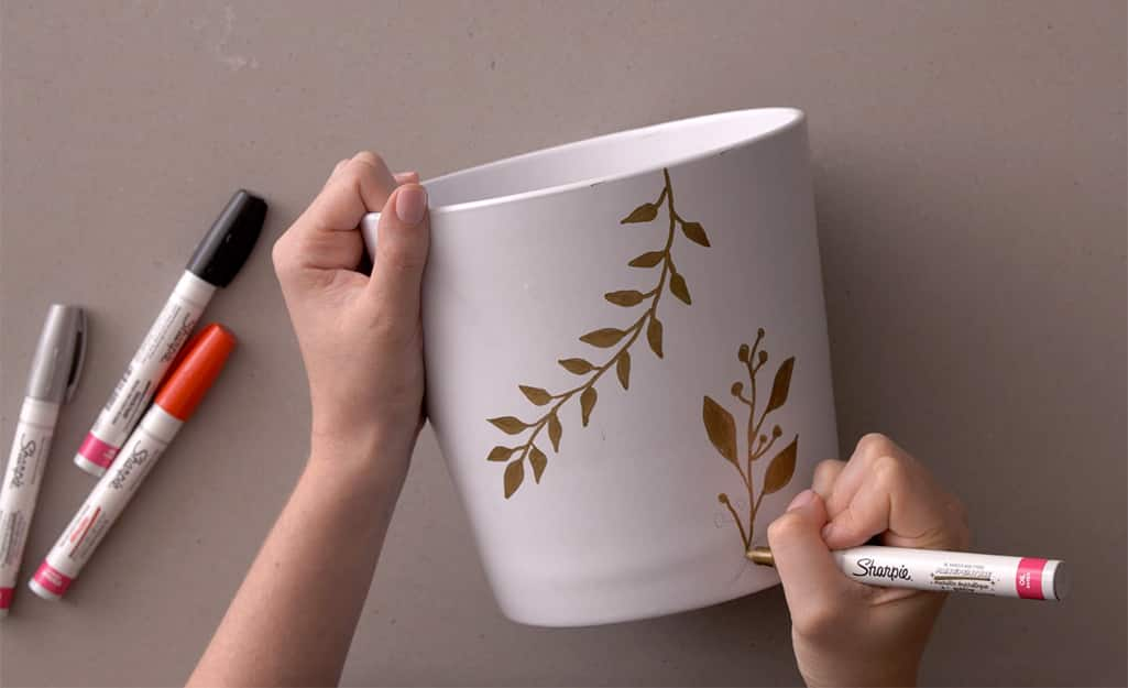 A gold marker is used to color in the stenciled pattern.