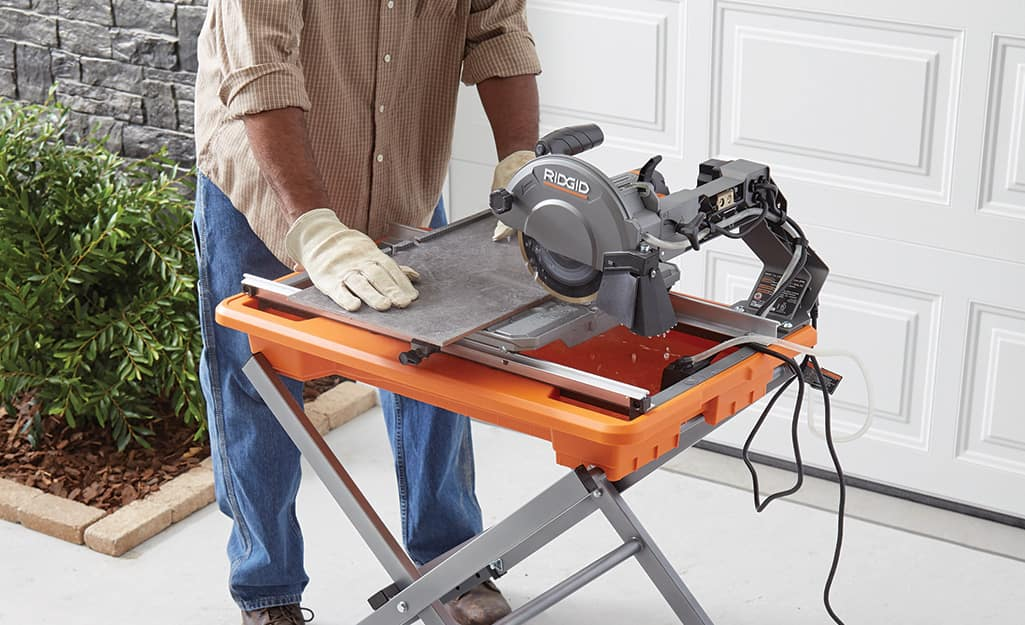 A person cuts tile with a wet saw.