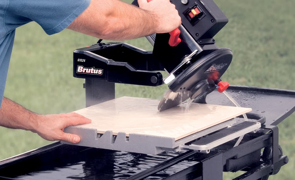 A person makes a bevel cut on a piece of tile with a wet saw.