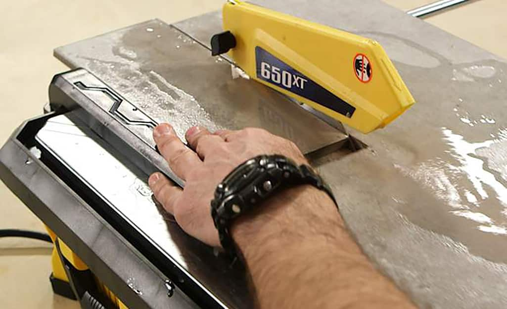 A person makes an L-shaped cut on a piece of time with a wet saw.