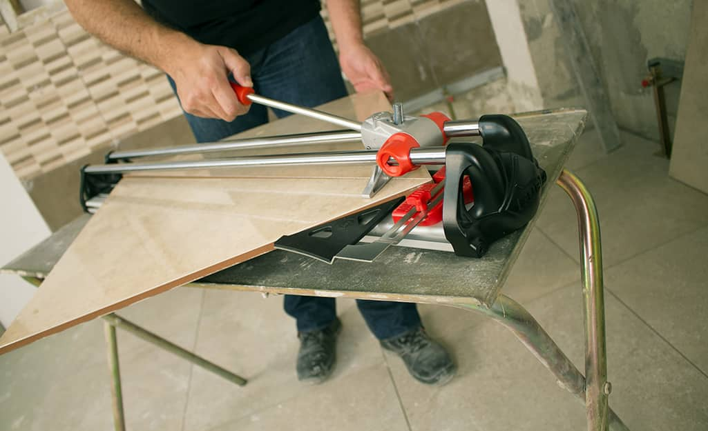 A person uses a manual tile cutter to cut a piece of tile.