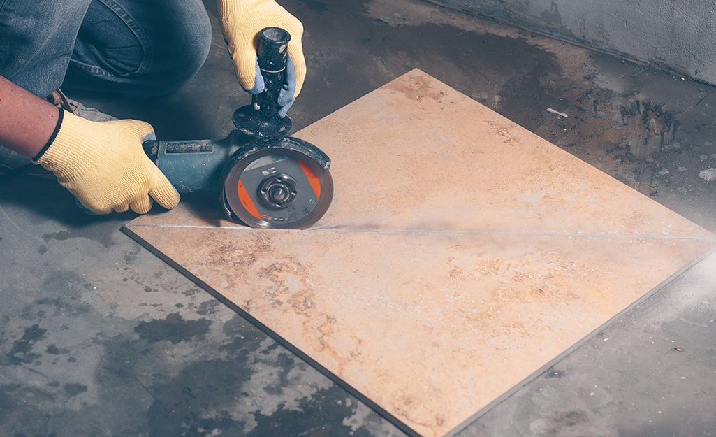 A person uses an angle grinder to cut a piece of tile.