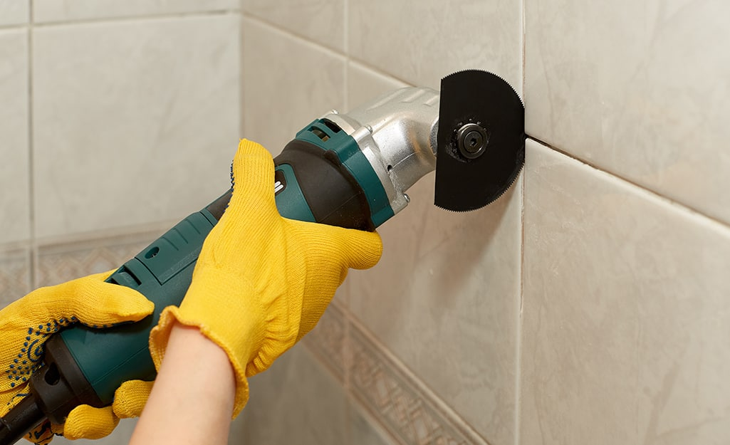 A person uses an angle grinder to cut a piece of style that's still on a bathroom wall.