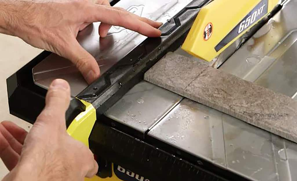 A person aligns a piece of tile before cutting with a wet saw.