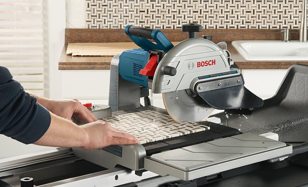 A person cuts a piece of tile with a wet saw.