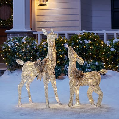 A front yard Christmas light display with reindeer.