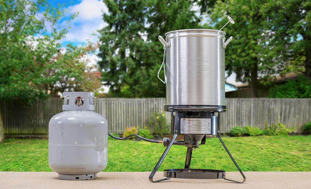 A turkey fryer and propane tank stand on a patio.