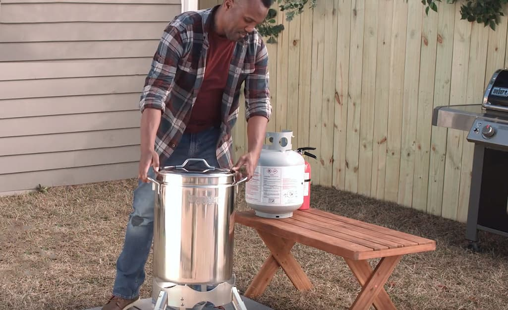 A person setting up a turkey fryer outside.