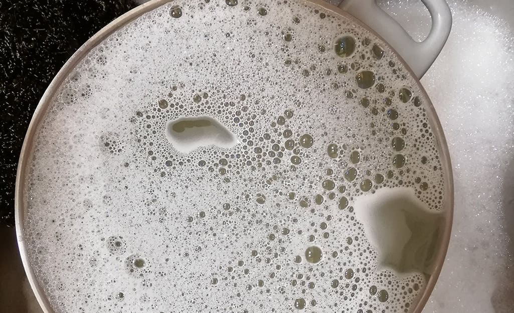 A turkey fryer pot filled with soapy water.