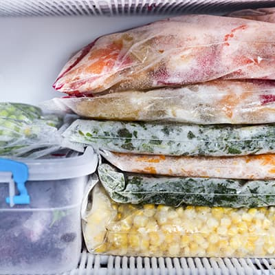 Frozen food stacked in a freezer.