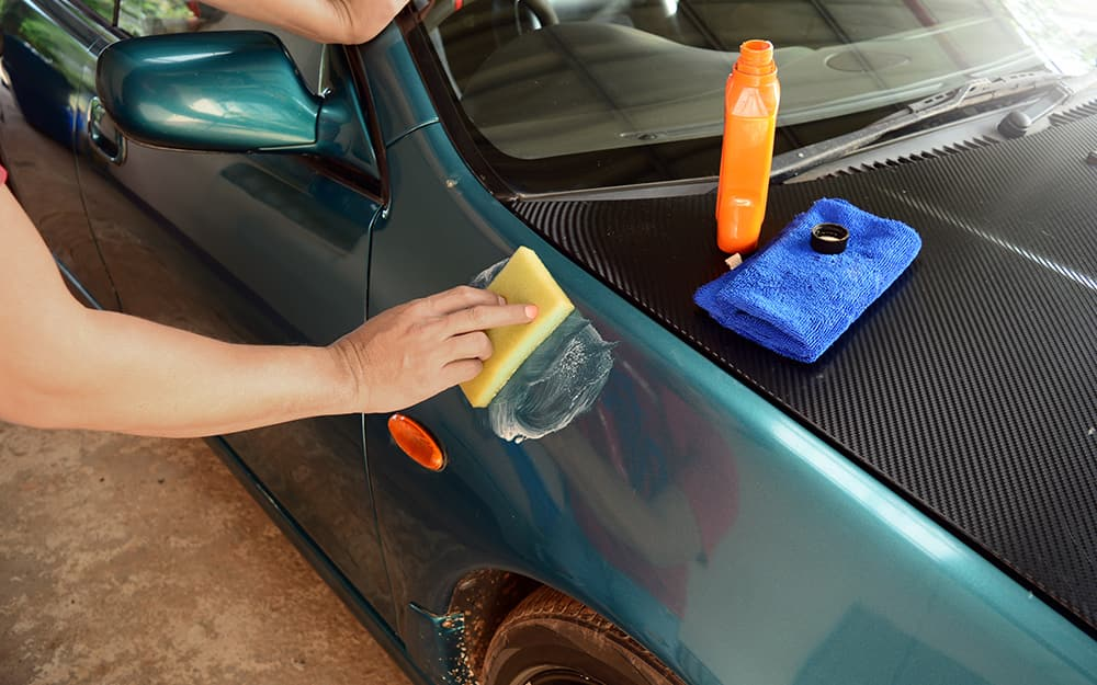 A person waxes the exterior of a car with an applicator pad.