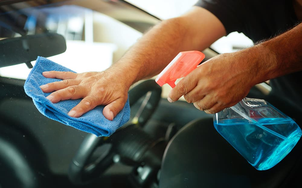 A person washes car windows with a cloth and glass cleaner.
