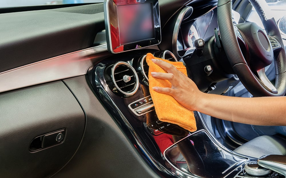 A person dusts the dashboard of a car with a cloth.