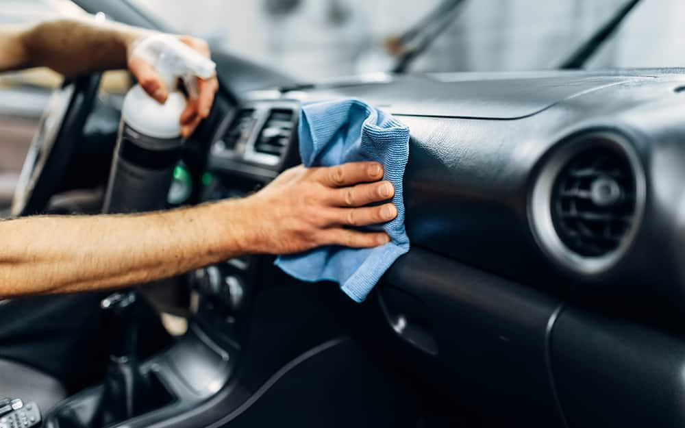 A person uses a cloth and spray cleaner to wash a car's dashboard.