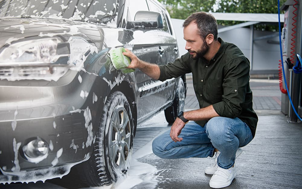 A person washes the exterior of a car with a sponge.
