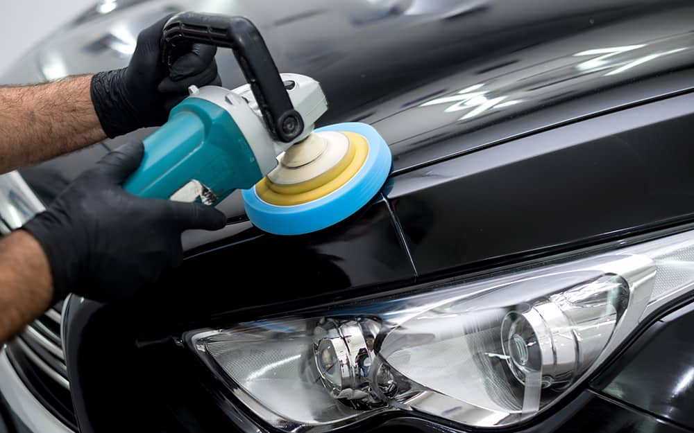 A person uses a power polisher on the exterior paint of a car.