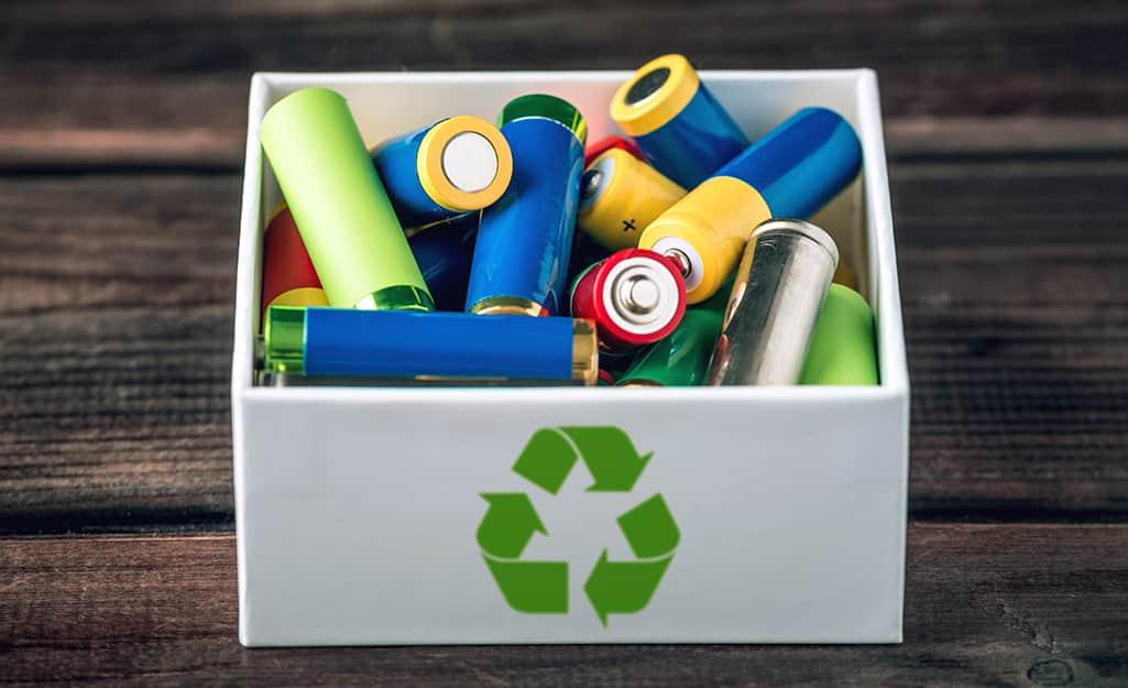 Batteries filling a recycling bin.
