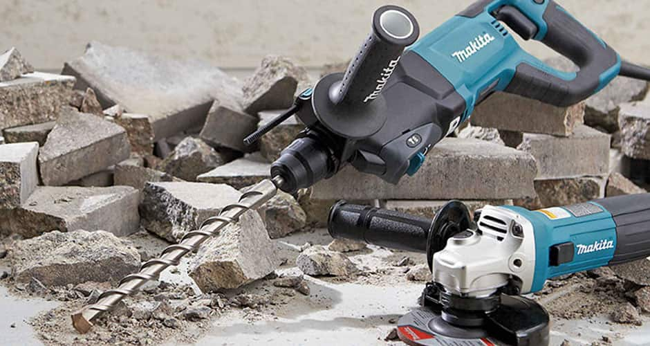 A hammer drill resting on the ground with pieces of broken concrete.