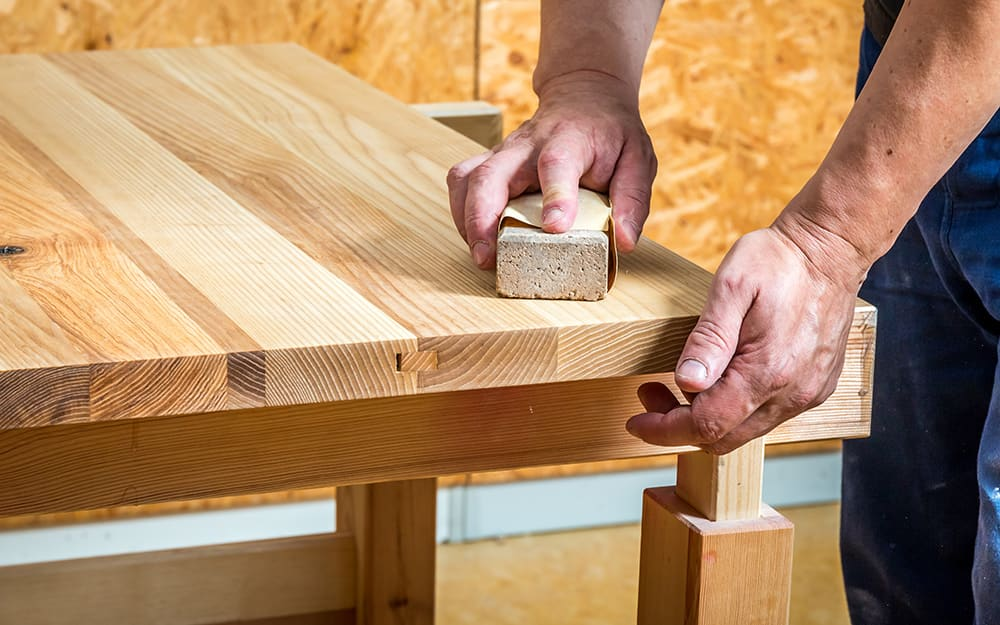 A person sanding a wood tabletop.