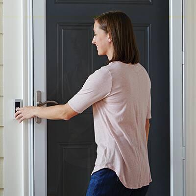 woman pressing a doorbell