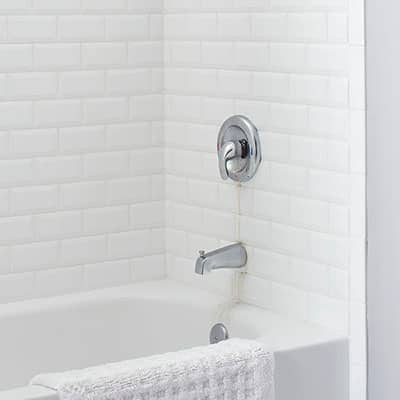 A standard bathtub featuring a single handle faucet with leak stains.