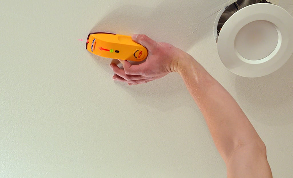 Hand placing stud finder along a ceiling to prepare to frame a new wall.