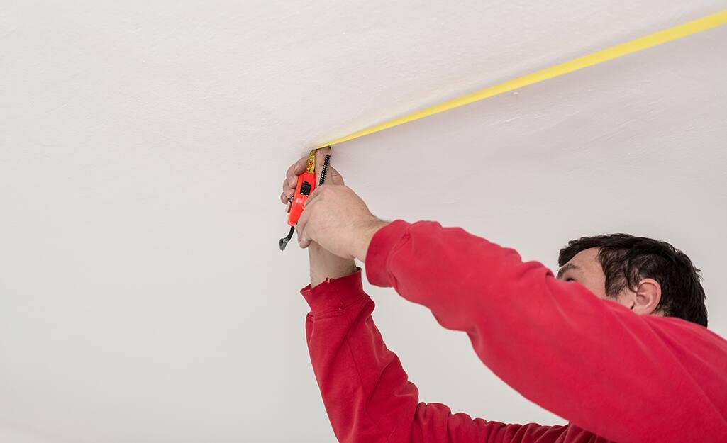 Person measuring corner wall mark.