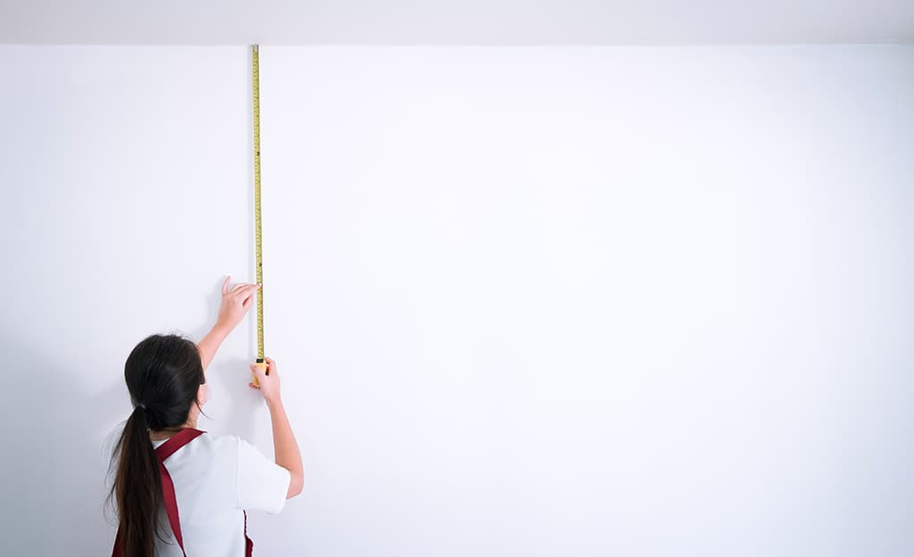 Person measuring stud length between ceiling and floor with tape measure.