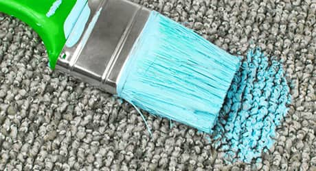 A paint brush soaked in blue paint next to dried paint stain on carpet.