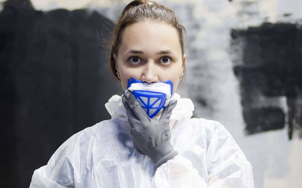 A person putting on a respirator face mask to avoid mold exposure.