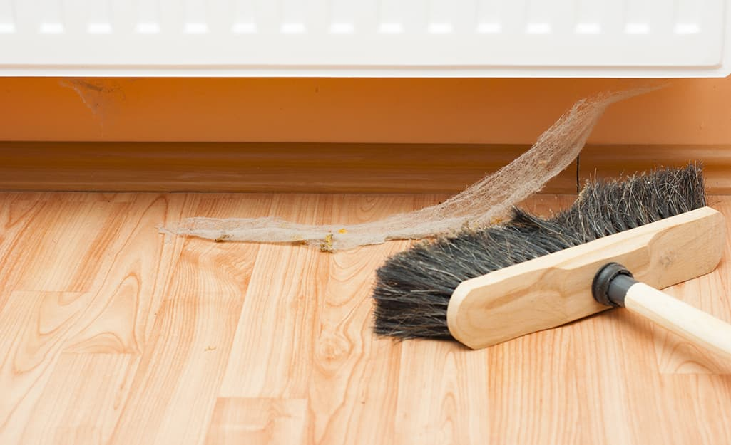 A person uses a push broom to sweep up a cobweb.