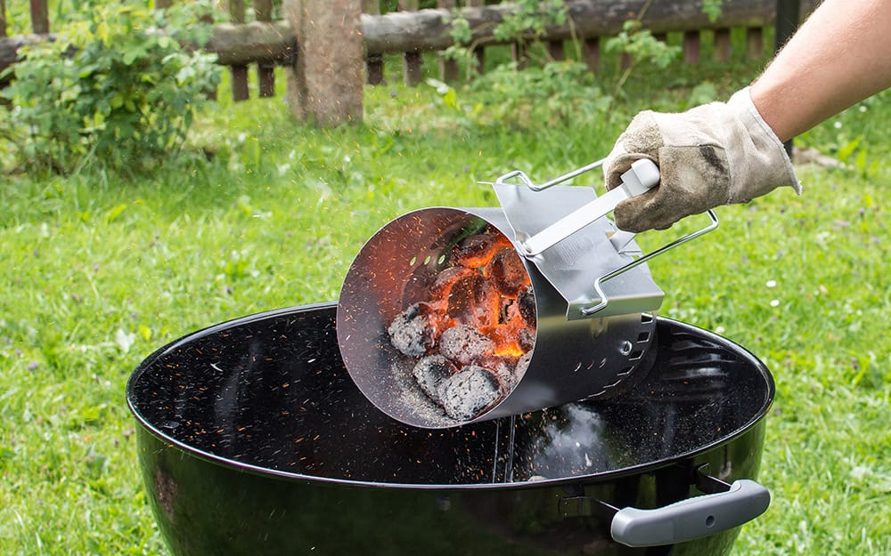 A person pouring hot charcoal into a grill.