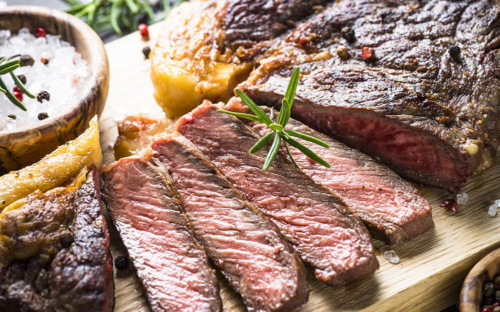 Freshly sliced grilled steak on a cutting board.