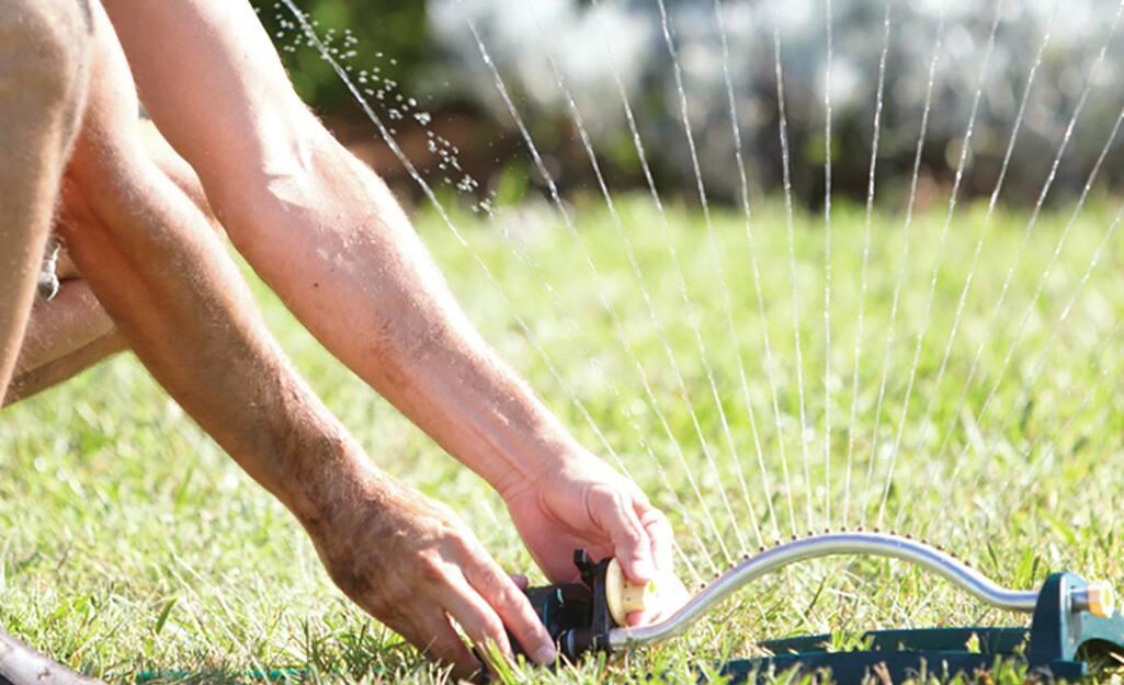 A person adjusting a lawn sprinkler.