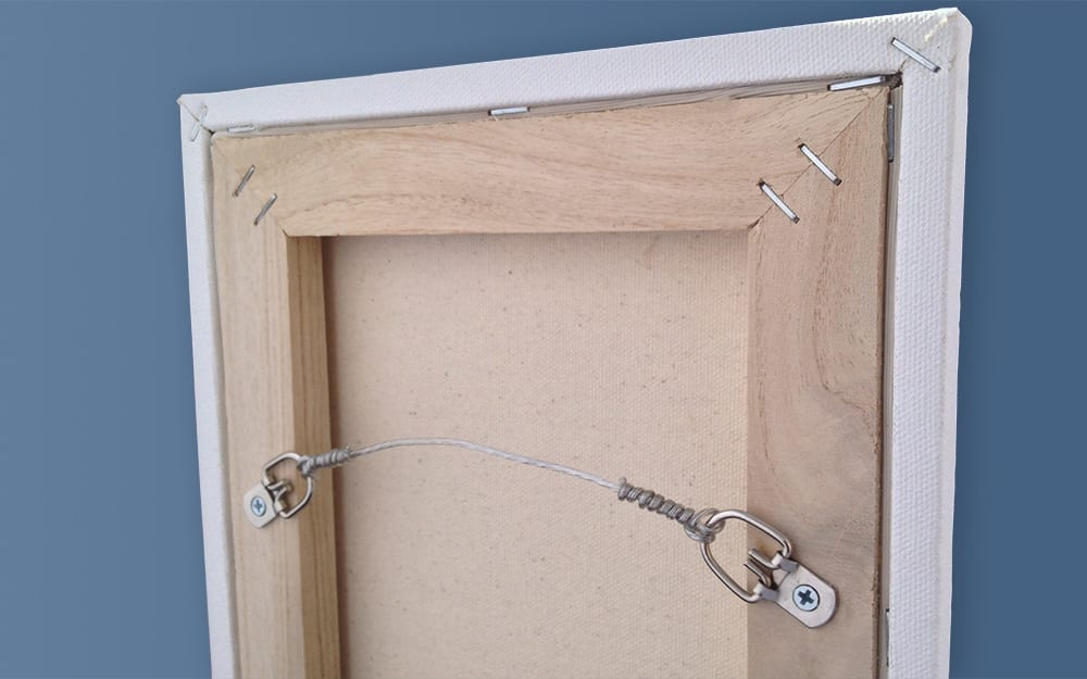 Picture wire strung between two D-rings attached to the back of a picture frame.