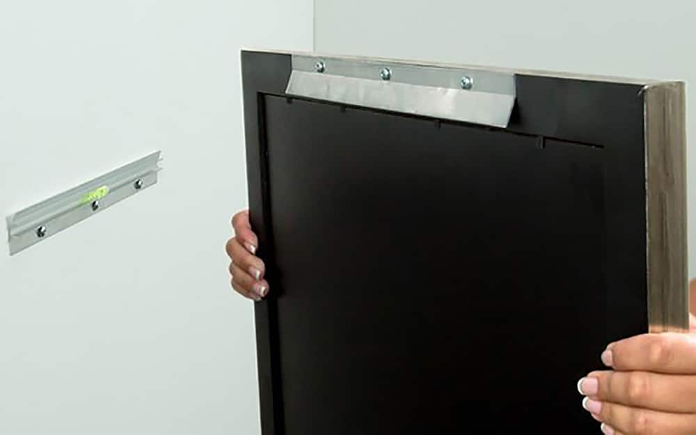 Interlocking metal brackets called French cleats are attached to a wall and the back of frame for easy hanging.