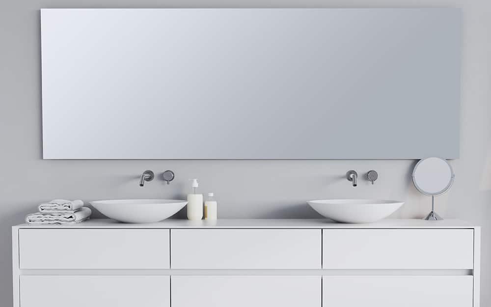 A large frameless mirror is hung on a bathroom wall behind a bathtub.