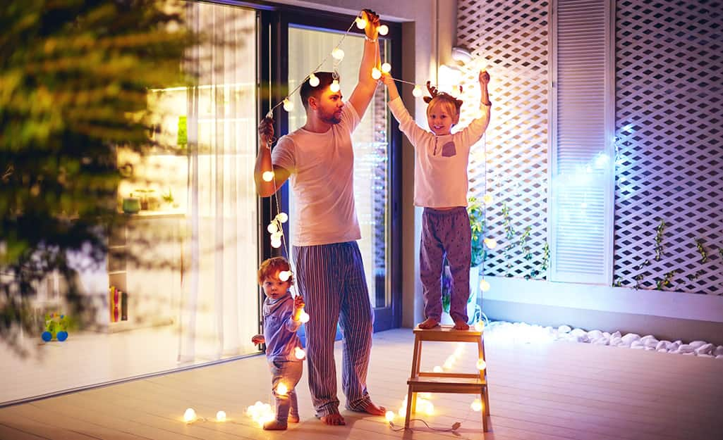 A family hanging Christmas lights outdoors.
