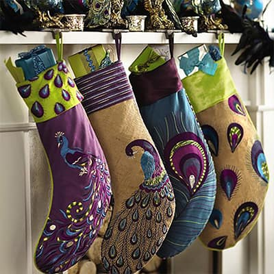 Christmas stockings decorated with peacocks hangs on a mantel.