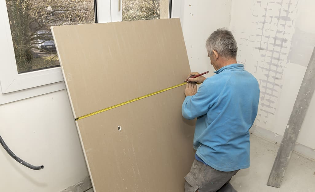 Person measuring and marking drywall.