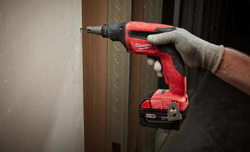 Person using a drill to screw drywall into a wall.