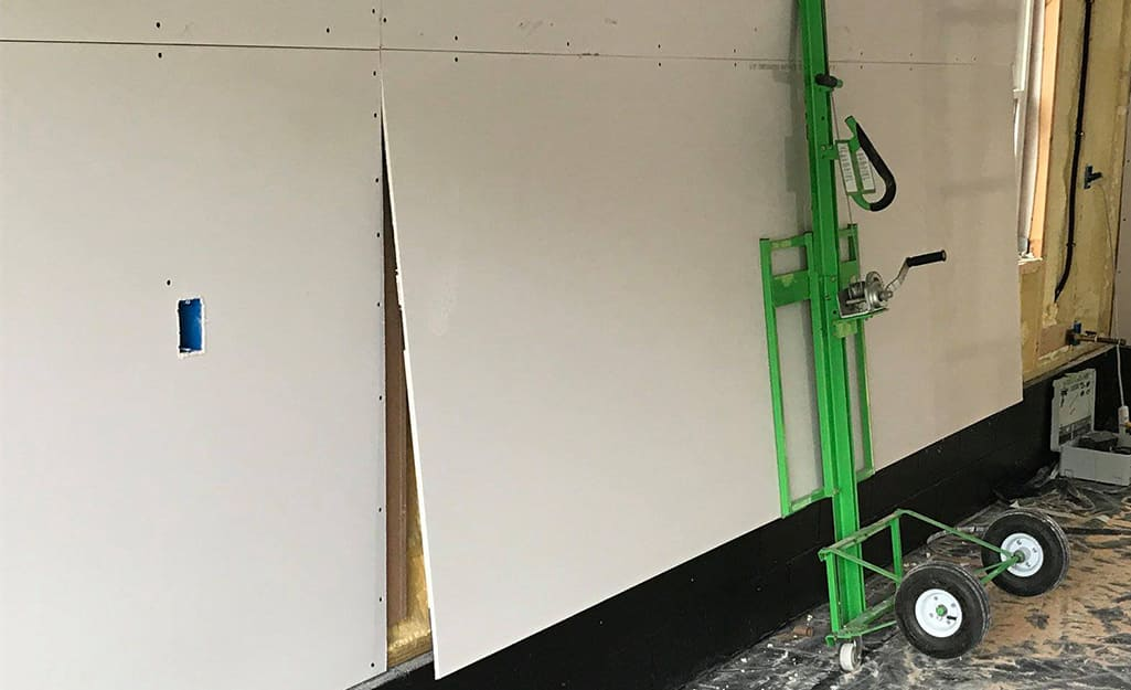 More drywall being placed on a wall using a drywall lift.