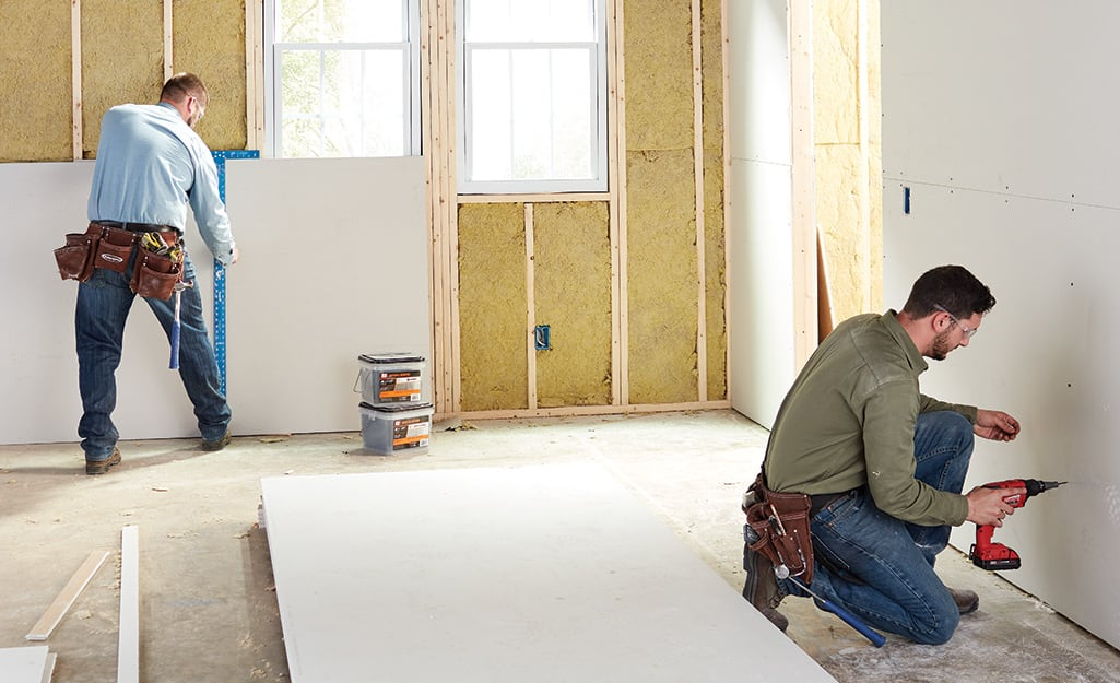 Two people installing drywall.