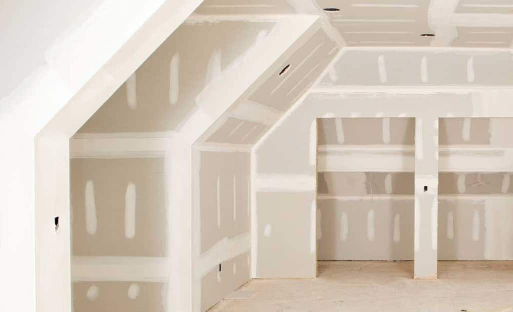 A room with unfinished drywall walls and ceiling.